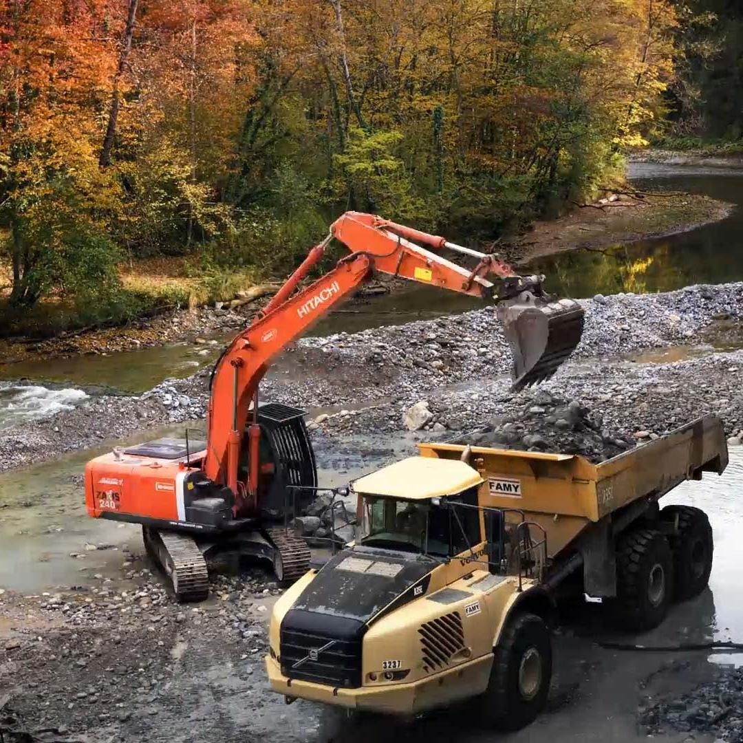 Travaux de restauration De La Continuité Écologique Du Chéran, pelleteuse et camion au milieu d'un paysage de rivière avec pierres nature Arbres Rivière